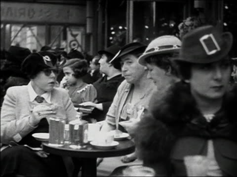 1930s b/w ms wealthy women sitting and eating at outdoor cafe / paris, france - french culture video stock e b–roll