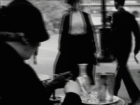 vídeos de stock, filmes e b-roll de 1930s b/w cu woman eating at outdoor cafe / paris, france - 1930