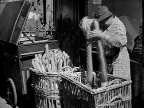 vídeos de stock, filmes e b-roll de 1930s b/w ms woman sorting loaves of french bread and placing them in her cart / paris, france - french culture