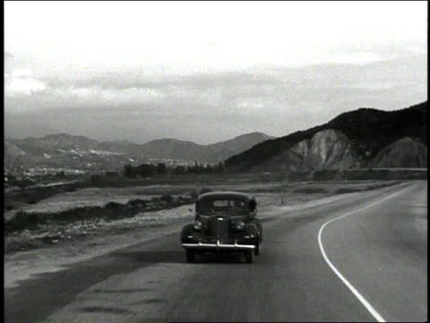 1930s DS car driving on a road / United States