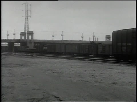 1930s ts car driving through a train yard while a man shoots a gun out of a window - shunting yard stock videos and b-roll footage