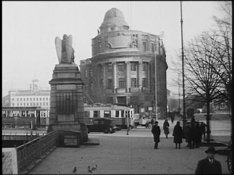 b/w 1930s car point of view on street with people toward building with traffic + trolley in front /vienna, austria - vienna austria stock videos & royalty-free footage