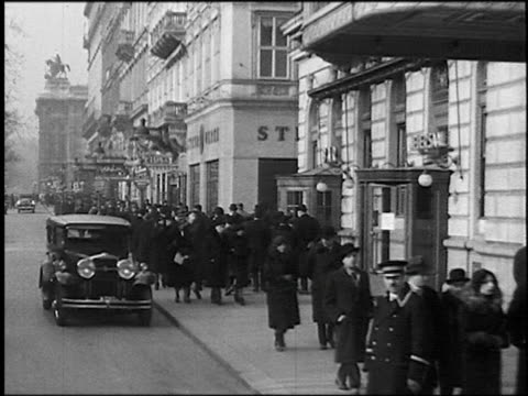 B/W 1930s car point of view past crowds on busy sidewalk + Grand Hotel on Karntner-Ring (street) / Vienna