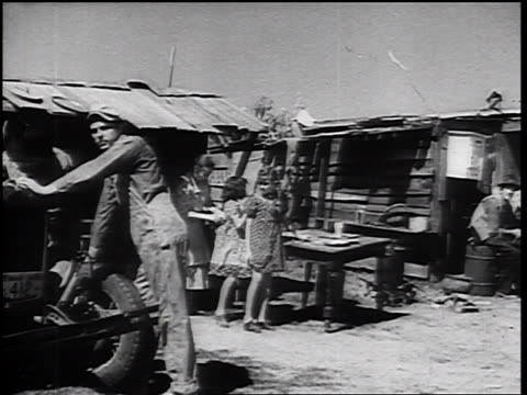 vidéos et rushes de b/w 1930s car point of view past shacks shantytown inhabitants looking at camera - bidonville
