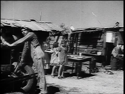 vidéos et rushes de b/w 1930s car point of view past shacks shantytown inhabitants looking at camera - la grande dépression
