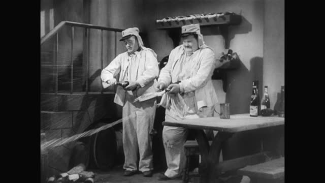 1930s champagne bottles aid laurel and hardy in their escape - 1930 1939点の映像素材/bロール