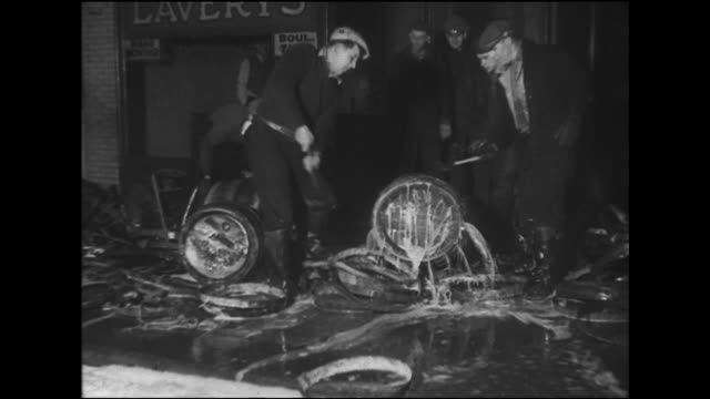 vidéos et rushes de government dry agents raiding garage warehouse on south halsted street, smashing barrels w/ sledge hammers, on sides, standing upright, lots of beer... - prohibition