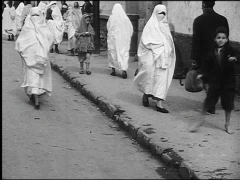 b/w 1930s children + muslim women in veils walking on city sidewalk / algiers, algeria - アルジェリア点の映像素材/bロール