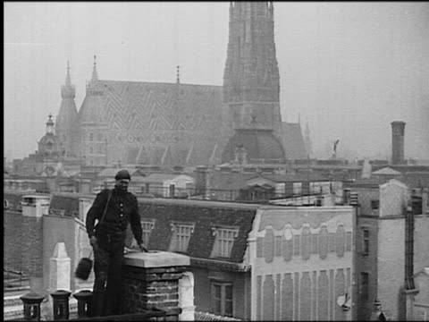 B/W 1930s chimney sweep climbs down from chimney / St Stephen's Cathedral in background / Vienna, Austria