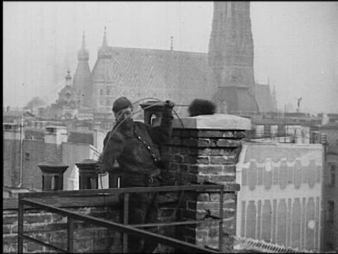 B/W 1930s chimney sweep guiding brush on wire into chimney / St Stephen's Cathedral in background / Vienna