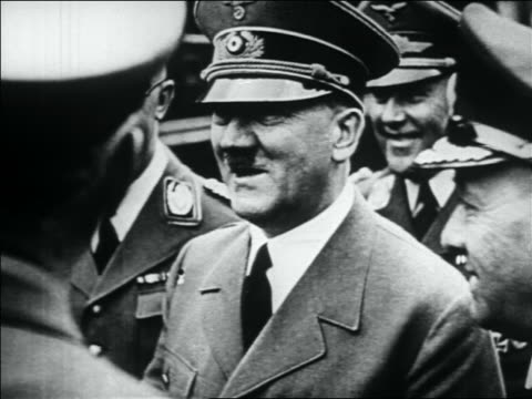 B/W 1930s close up Adolf Hitler in uniform smiling talking to men surrounding him