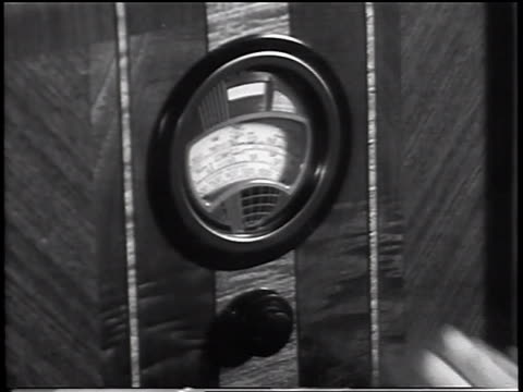 B/W 1930s close up hand on radio dial / industrial