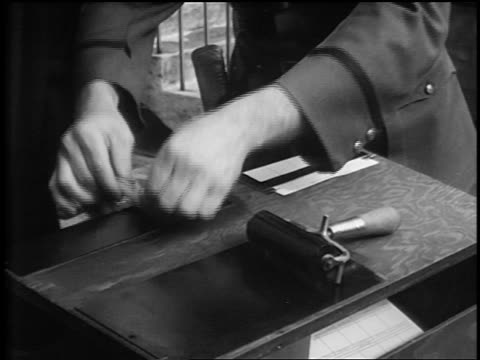 B/W 1930s close up hands of Amelia Earhart being fingerprinted by policeman / newsreel