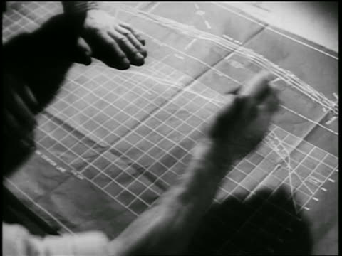 B/W 1930s close up hands of two men writing on blueprints / documentary