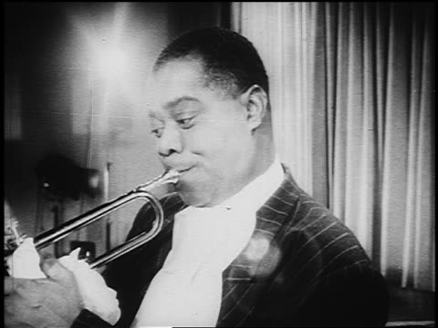b/w 1930s close up louis armstrong playing trumpet indoors - アメリカ黒人の歴史点の映像素材/bロール