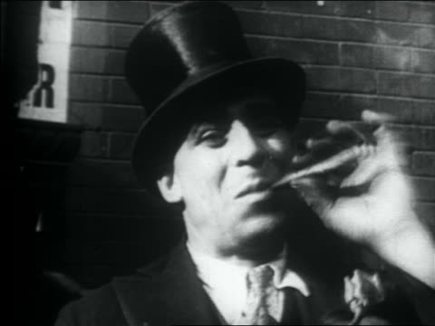 b/w 1930s close up man in top hat smoking cigar outdoors - sigaro video stock e b–roll