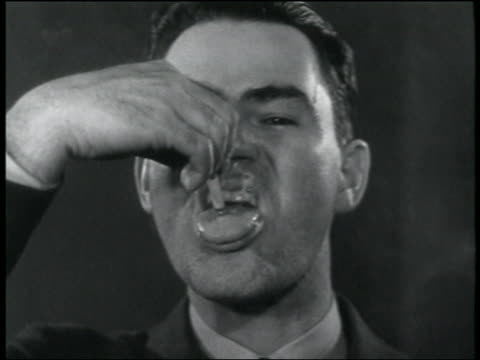 b/w 1930s close up man smoking cigarette + putting it out on his tongue - stunt person stock videos & royalty-free footage