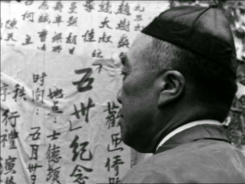 vídeos y material grabado en eventos de stock de b/w 1930s close up over-the-shoulder man reading chinese news posted on wall / chinatown, san francisco / travelogue - only mature men