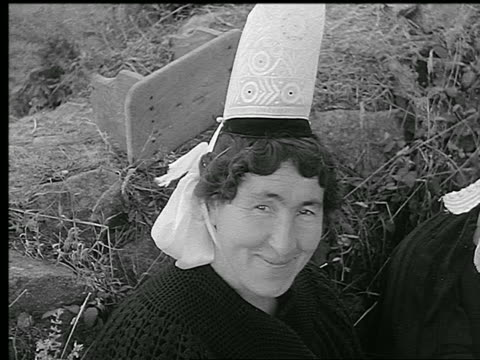 b/w 1930s close up portrait middle-aged woman in traditional lace hat smiling outdoors / brittany, france - ブルターニュ点の映像素材/bロール