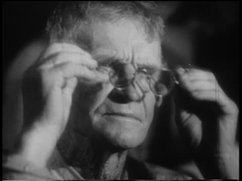 B/W 1930s close up PORTRAIT senior man putting on eyeglasses looking sad during Great Depression