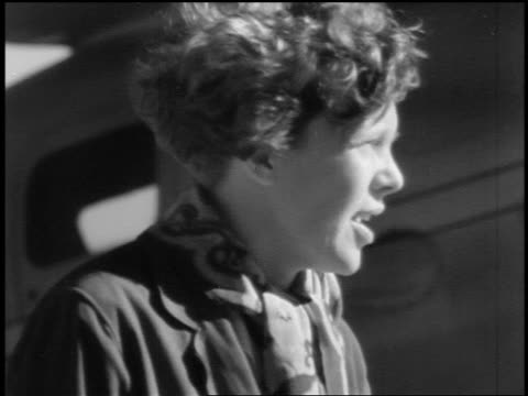 B/W 1930s close up PROFILE Amelia Earhart talking outdoors with aircraft in background
