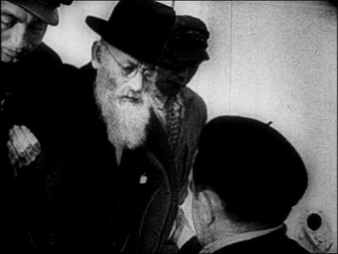 b/w 1930s close up senior jewish man being pushed dragged / nazi takeover of germany - judaism stock-videos und b-roll-filmmaterial