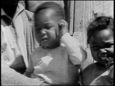 b/w 1930s close up small black boy yawning + scratching ear as mother holds him / alabama / documentary - single mother stock videos & royalty-free footage