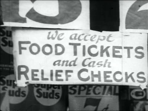 b/w 1930s close up we accept food tickets and cash relief checks sign / great depression - new deal video stock e b–roll