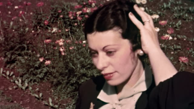 1930s close up woman removing hat and fixing hair / turning head to show hairstyle / flowers in background
