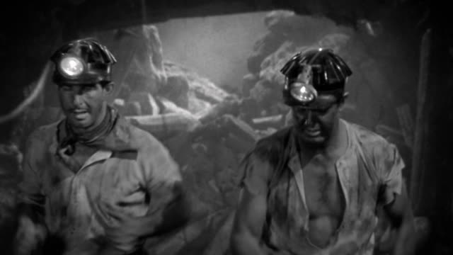 1930s composite medium shot 2 miners running from collapse / explosions in background / STAGED