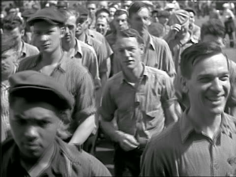 b/w 1930s crowd of male blue collar workers walking towards camera to enter factory - occupazione industriale video stock e b–roll
