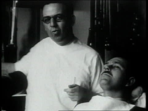 1930s cu dentist working on patient's teeth and eating at the same time - dentist stock videos & royalty-free footage