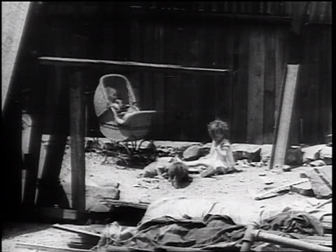 vidéos et rushes de b/w 1930s doll in carriage toddler sitting in pile of refuse by wooden fence - une seule petite fille