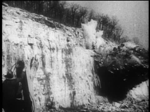 vídeos de stock, filmes e b-roll de b/w 1930s explosion on side of hill in dam construction / tennessee river valley - nova negociação