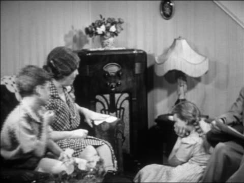 vidéos et rushes de b/w 1930s family sitting in living room listening to radio / educational - 1930