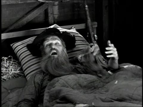 1930s ha farmer sleeping in a bed with a goat / united states - ヒルビリー点の映像素材/bロール