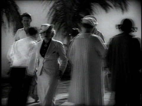 1930s TS fashionably dressed people walking through a courtyard with palm trees in it / Miami, Florida, United States
