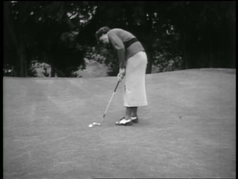 b/w 1930s pan female golfer putting ball into hole - golf shoe stock videos & royalty-free footage