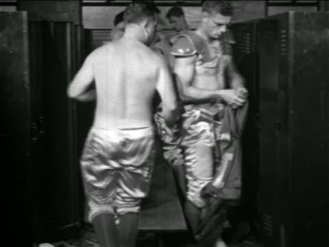 B/W 1930s football players putting on padding uniforms in locker room / Detroit Lions