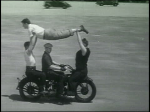 b/w 1930s four people on moving motorcycle / two hold one man up in air - stunt person stock videos & royalty-free footage