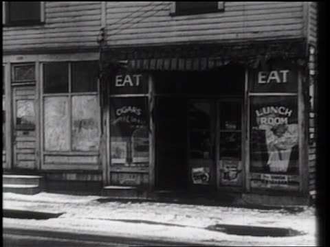b/w 1930s pan from luncheonette on deserted street of town in winter to man walking / industrial - 1930 stock videos and b-roll footage