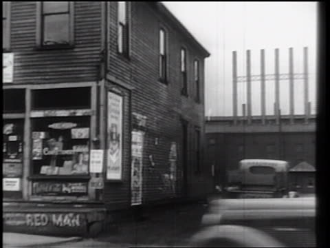 B/W 1930s PAN from luncheonette to truck driving towards factory / industrial