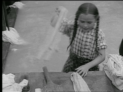 b/w 1930s ms girl in braids scrubbing clothes next to basin + smiling to camera / brittany, france - only girls stock videos and b-roll footage