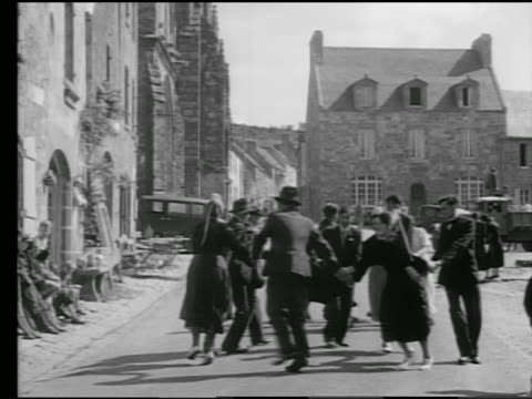 b/w 1930s group doing circle dance in village wedding celebration / locronan, brittany, france - ブルターニュ点の映像素材/bロール