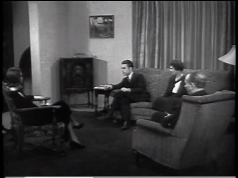 vidéos et rushes de b/w 1930s group of people sitting in living room listening to radio / industrial - poste de radio