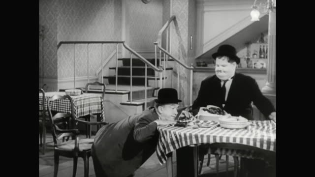 1930s hardy makes sitting at the table difficult for laurel - 1930 1939 stock-videos und b-roll-filmmaterial