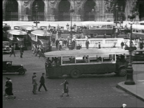 vidéos et rushes de b/w 1930s high angle pan bus in traffic through busy intersection / people walking on sidewalks / paris - 1930