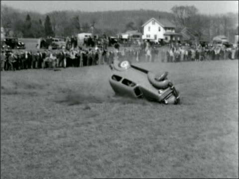 b/w 1930s high angle car skidding + flipping over in field with audience watching - 横滑り点の映像素材/bロール