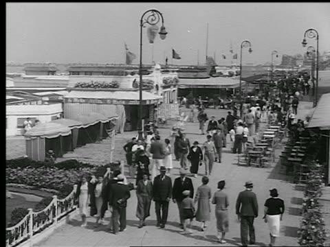 vidéos et rushes de b/w 1930s high angle crowd of people walking on boardwalk / deauville, normandy, france - station de vacances
