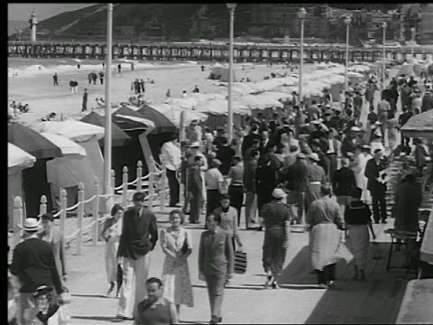 b/w 1930s high angle crowd of people walking on boardwalk / ocean + beach in bg/ deauville, normandy, france - tourist resort stock videos and b-roll footage